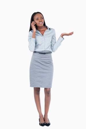 Portrait of a confused businesswoman making a phone call against a white background photo