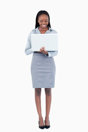 Portrait of a smiling businesswoman using a laptop while standing up against a white background Stock Photo - 11624114
