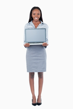 Portrait of a cute businesswoman showing a laptop against a white background photo
