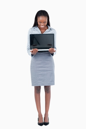 Portrait of a businesswoman showing a laptop against a white background photo