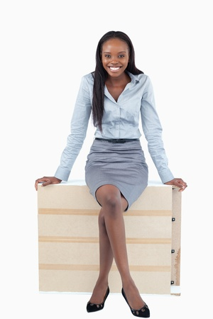 Portrait of a smiling businesswoman sitting on a panel against a white background photo