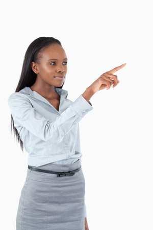 access point: Portrait of a young businesswoman pressing an invisible key against a white background