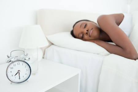 Woman sleeping while her alarm clock is ringing in her bedroom photo