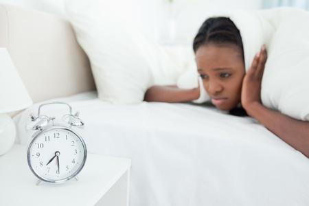 obudził: Kobieta jest budzony przez jej budzika w swojej sypialni