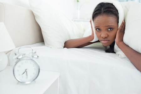awakened: Young woman being awakened by her alarm clock in her bedroom