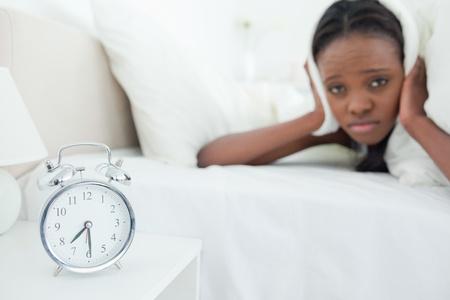 awakened: Cute woman being awakened by her alarm clock in her bedroom Stock Photo