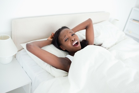 Woman yawning on her bed while looking at the camera photo