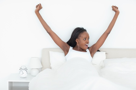 Woman stretching her arms in her bedroom Stock Photo