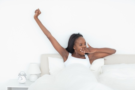 Woman stretching her arms and yawning in her bedroom photo