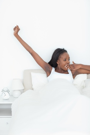 Portrait of a woman stretching her arms and yawning in her bedroom photo