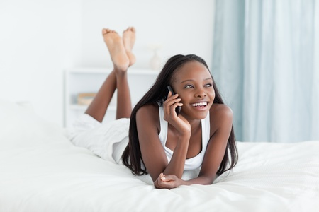 Happy woman making a phone call in her bedroom photo