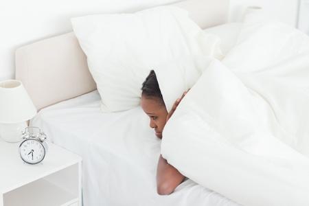 obudził: Nieszczęśliwa kobieta jest obudzony przez budzik w swojej sypialni Zdjęcie Seryjne