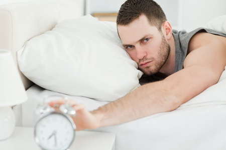 Man switching off his alarm clock in his bedroom photo