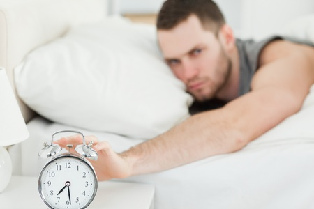 Unhappy man switching off his alarm clock in his bedroom photo