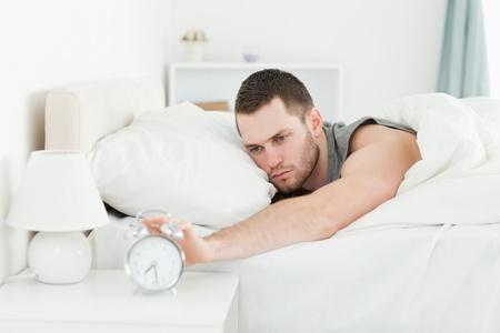 Exhausted man switching off his alarm clock in his bedroom photo