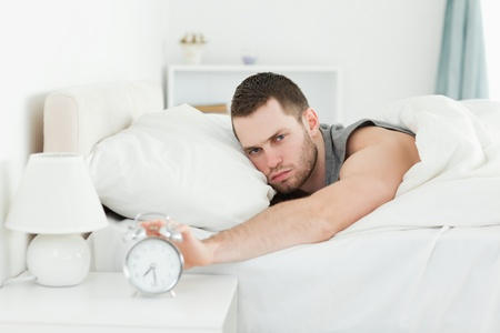Tired young man switching off his alarm clock in his bedroom photo