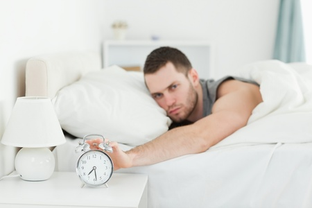 Man being awakened by an alarm clock in his bedroom photo