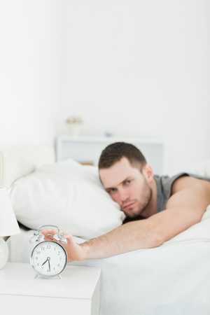 Portrait of a man being awakened by an alarm clock in his bedroom photo
