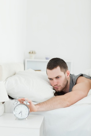 awakened: Portrait of a unhappy man being awakened by an alarm clock in his bedroom Stock Photo