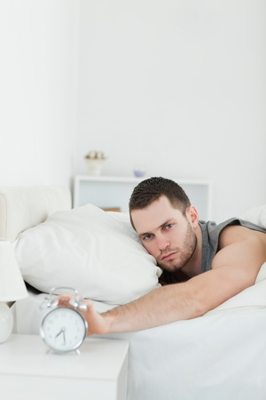 awakened: Portrait of a handsome man being awakened by an alarm clock in his bedroom