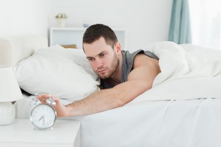 awakened: Tired man being awakened by an alarm clock in his bedroom