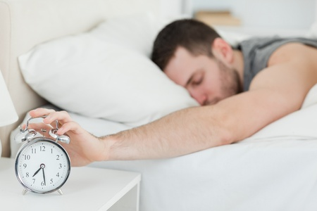 up wake: Exhausted man being awakened by an alarm clock in his bedroom