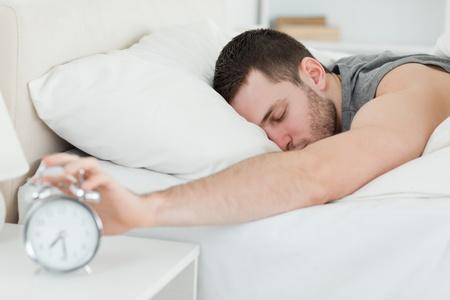 Sleeping man being awakened by an alarm clock in his bedroom
