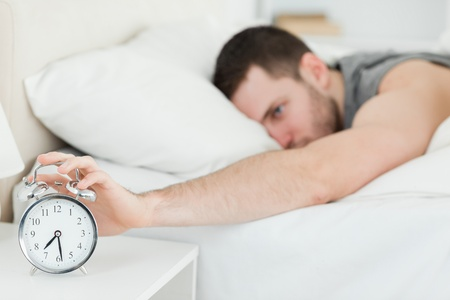 Brown-haired man being awakened by an alarm clock in his bedroom photo