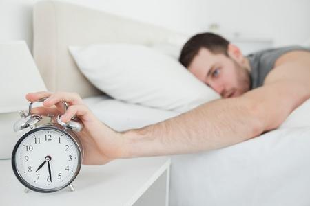 obudził: Młody człowiek jest obudzony przez budzik w swojej sypialni Zdjęcie Seryjne