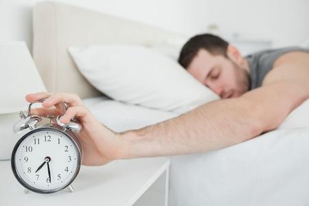 obudził: Spanie młody człowiek jest obudzony przez budzik w sypialni