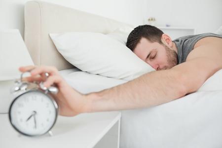 awakened: Sleeping handsome man being awakened by an alarm clock in his bedroom