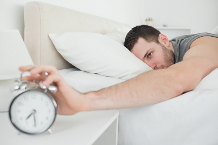 Sleeping attractive man being awakened by an alarm clock in his bedroom photo