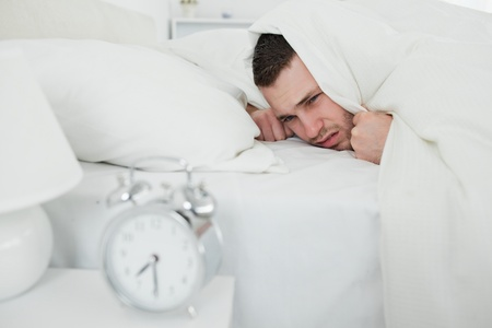 Man covering his ears while his alarm clock is ringing in his bedroom photo