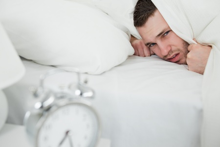 Annoyed man covering his ears while his alarm clock is ringing in his bedroom photo