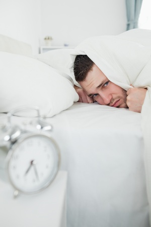 Portrait of a man covering his ears while his alarm clock is ringing in his bedroom photo