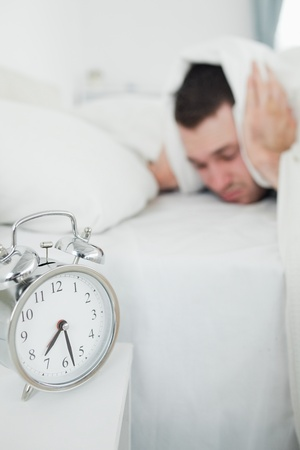 Portrait of an attractive man covering his ears while his alarm clock is ringing in his bedroom photo
