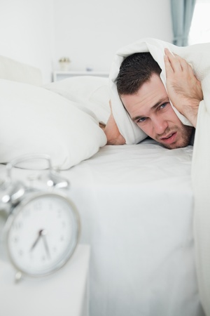 Portrait of a man covering his ears with a duvet while his alarm clock is ringing in his bedroom photo