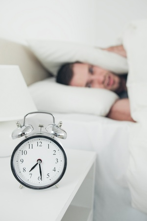 Portrait of an attractive young man covering his ears while his alarm clock is ringing in his bedroom photo