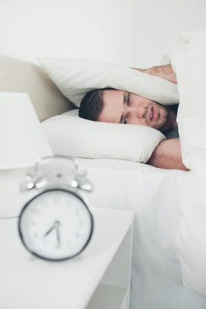 Portrait of a beautiful young man covering his ears while his alarm clock is ringing in his bedroom photo