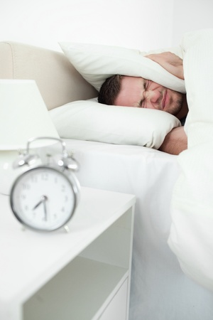 Portrait of a young man covering his ears with a pillow while his alarm clock in ringing photo