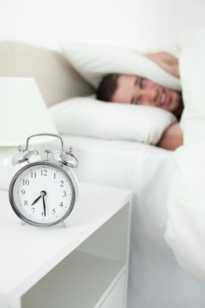Portrait of a exhausted man covering his ears with a pillow while his alarm clock is ringing photo