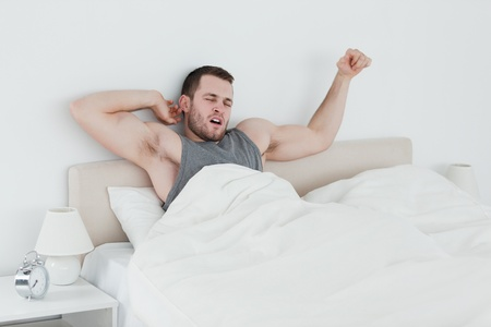Man stretching his arms in his bedroom photo