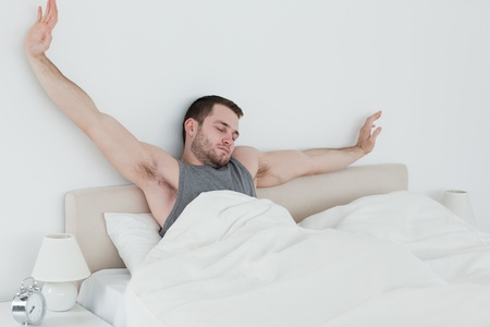Tired man stretching his arms in his bedroom photo