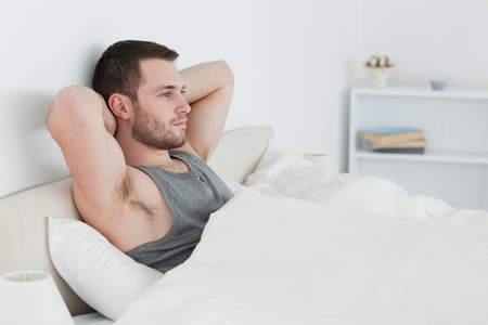 Young man waking up in his bedroom Stock Photo - 11634793