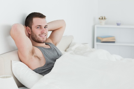 Smiling man waking up in his bedroom photo