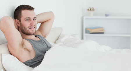 Handsome man waking up in his bedroom Stock Photo - 11636921