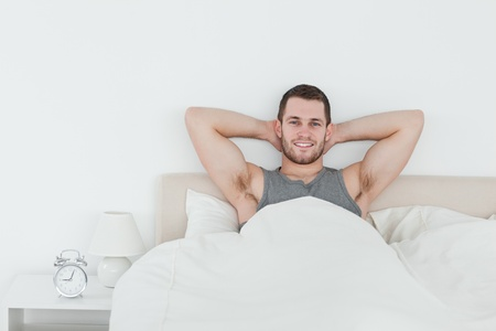 Happy man waking up in his bedroom photo