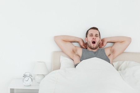 Man yawning while waking up in his bedroom photo