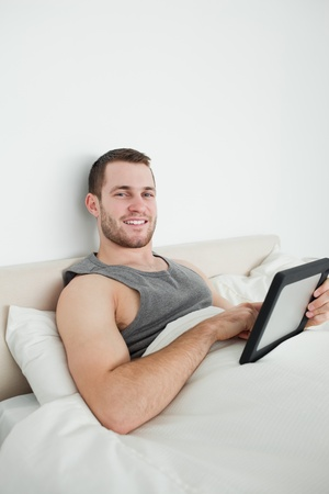 Portrait of a young man using a tablet computer in his bedroom photo