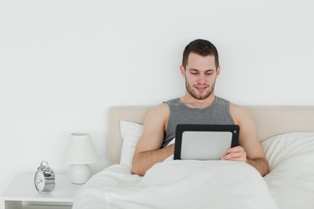Beautiful man using a tablet computer in his bedroom photo